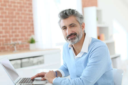 working from home: Trendy mature man working from home with laptop Stock Photo