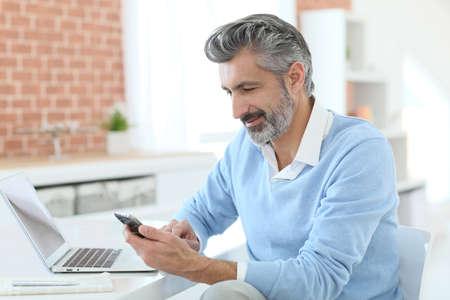 ノート パソコンの前でスマート フォンを使用して流行の成熟した男 写真素材 - 38127259