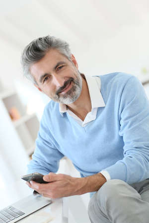 Trendy mature man using smartphone in front of laptop photo