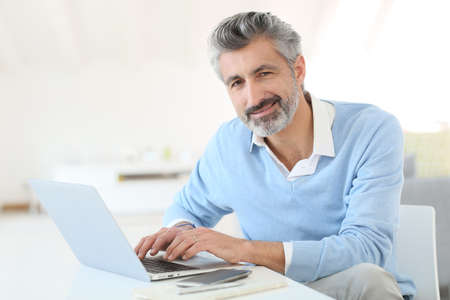 Trendy mature man working from home with laptop photo