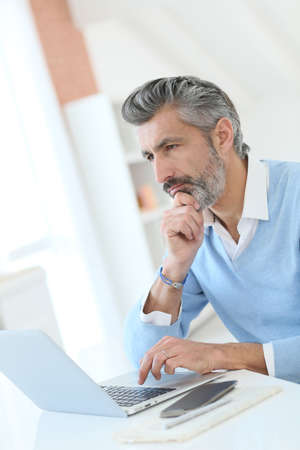 telework: Trendy mature man working from home with laptop Stock Photo
