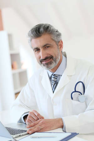 medicalcare: Doctor working in office on laptop