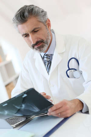 medicalcare: Doctor looking at X-ray results Stock Photo