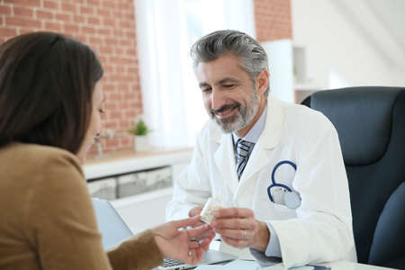 doctor giving pills: Doctor giving prescription to patient Stock Photo