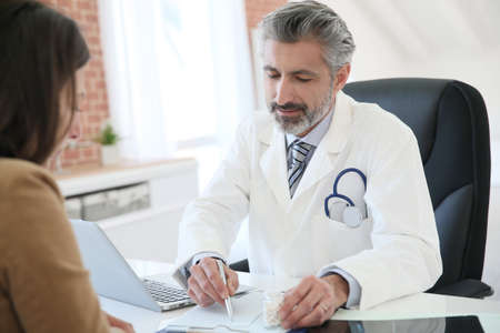 Doctor giving prescription to patient Stock Photo