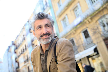 40s: Handsome mature man walking in town Stock Photo