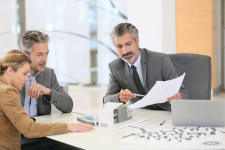 client meeting: Mature couple meeting architect for construction project Stock Photo