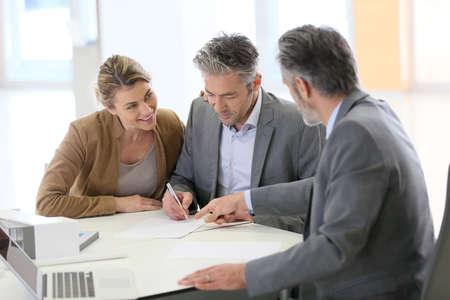 firmando: Contrato de construcción firma de los pares maduros en la oficina de arquitecto