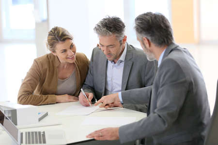 building planners: Mature couple signing construction contract in architects office