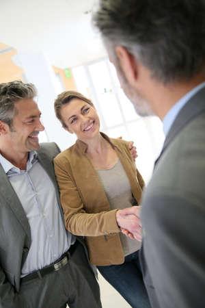 adviser: Adviser giving handshake to clients Stock Photo