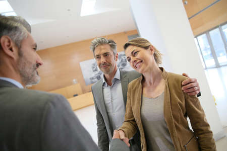 financial planner: Adviser giving handshake to clients Stock Photo