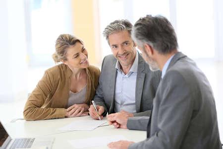 firmando: Pareja mayor firma de contrato financiero en el banco
