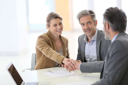 planner: Couple in bank office shaking hand to financial adviser