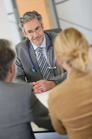 medicalcare: Senior doctor listening to patients in office
