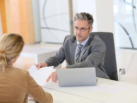 banker: Woman meeting with banker and signing contract Stock Photo