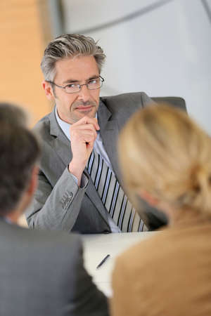 financial planning married: Consultant listening to clients in meeting