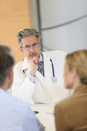 medicalcare: Doctor meeting couple in hospital office