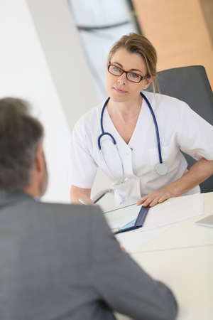 hospital patient: Doctor meeting with patient in hospital office Stock Photo