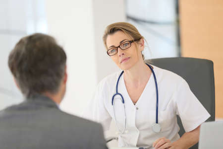 hospital: Doctor meeting with patient in hospital office Stock Photo