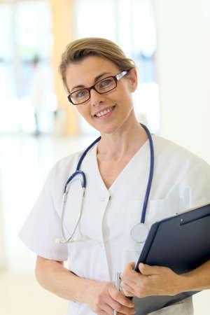 medicalcare: Confident mature nurse standing in hospital corridor Stock Photo