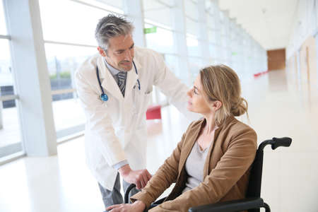 Doctor talking to woman in wheelchair after surgery Stockfoto