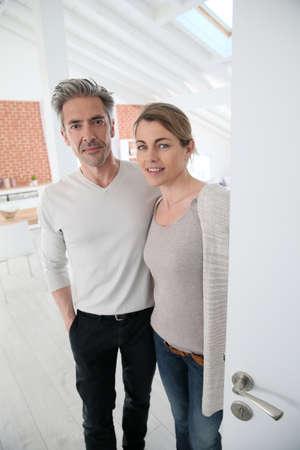 Älteres Paar öffnende Tür ihres Hauses Standard-Bild