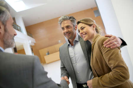 building planners: Adviser giving handshake to clients Stock Photo