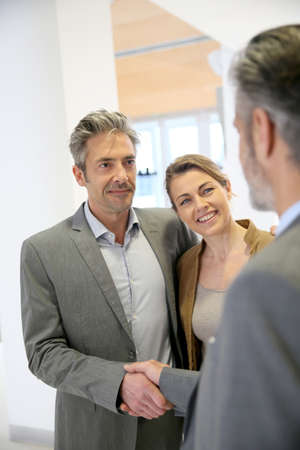 real estate planning: Adviser giving handshake to clients Stock Photo