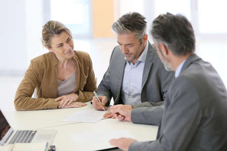 Mature couple signing financial contract at the bank photo