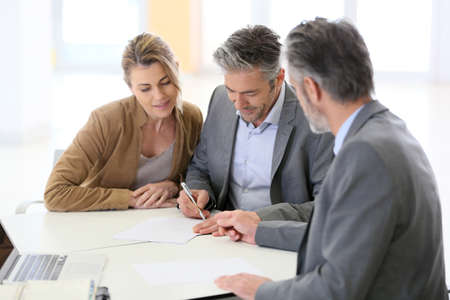 planner: Mature couple signing financial contract at the bank