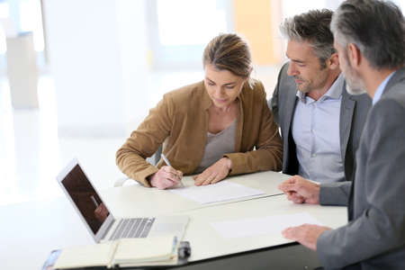 real estate contract: Mature couple signing financial contract at the bank