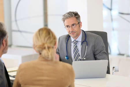 Senior doctor listening to patients in office