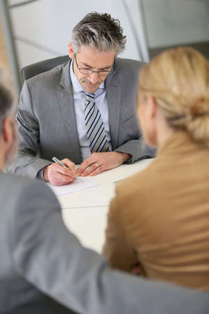 lawyer meeting: Mature couple signing contract in lawyers office