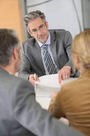 Mature couple signing contract in lawyers office