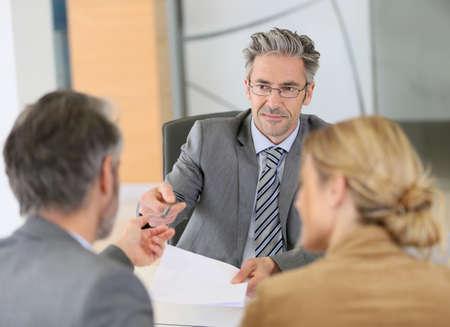 firmando: Contrato de firma de los pares maduros en la oficina del abogado