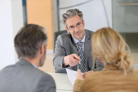 Ouder stel ondertekening van het contract in het kantoor van advocaat