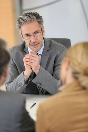 Consultant listening to clients in meeting photo
