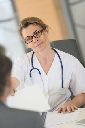 medicalcare: Doctor meeting with patient in hospital office Stock Photo