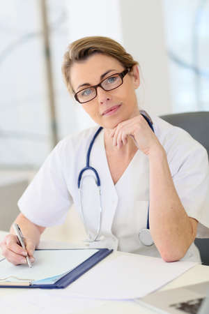 medicalcare: Portrait of mature nurse sitting at desk in office