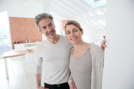 Mature couple opening door of their home Stock Photo