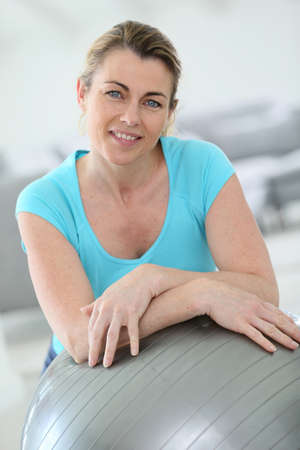Mature woman doing fitness exercises at home Stock Photo