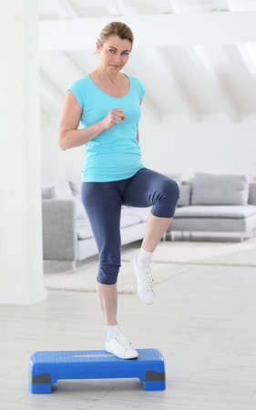 exercices: Middle-aged woman doing step exercices at home