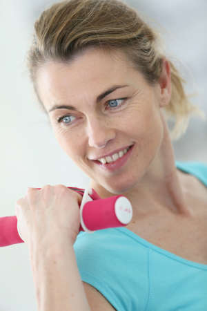 musculation: Portrait of mature fitness woman lifting dumbbells