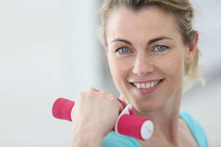 Portrait of mature fitness woman lifting dumbbells