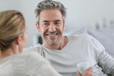 hombres maduros: Pareja mayor hablando juntos en el sofá