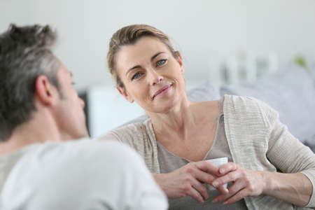Mature couple talking together in sofa Stock Photo