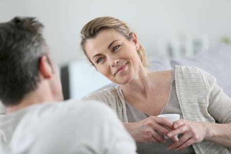 Couple d'âge mûr parler ensemble dans le canapé