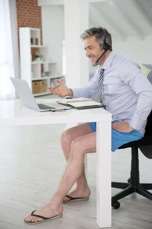 telework: Businessman on video meeting from home in relaxed outfit Stock Photo