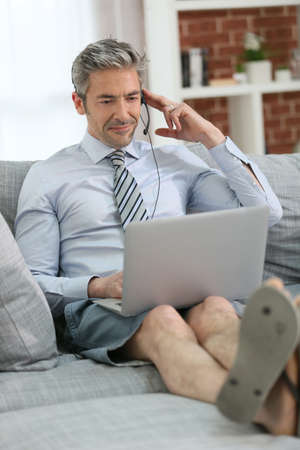working from home: Businessman with headset working from home on couch