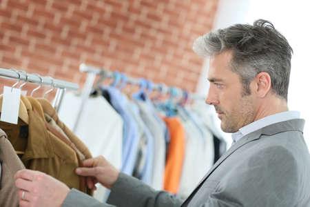 vestidos antiguos: Hombre maduro elegir ropa en tienda